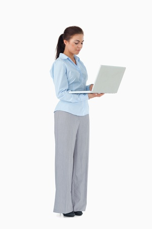 Young professional woman working on laptop against a white background photo