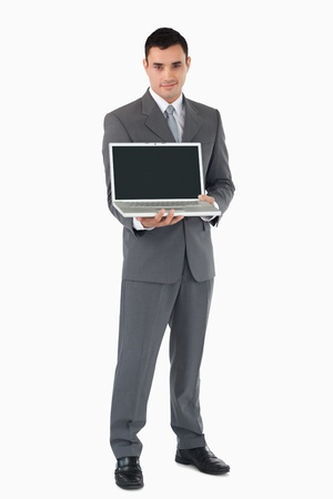 Confident businessman presenting his laptop against a white background photo