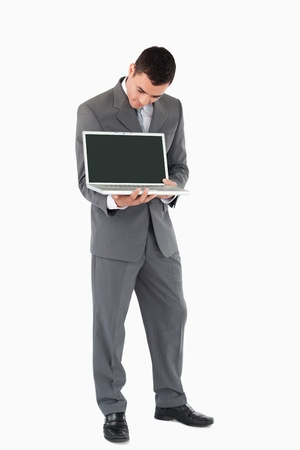 Young businessman showing whats on his screen against a white background photo