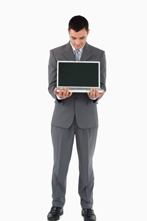 Young businessman standing with his laptop against a white background photo