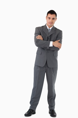Confident businessman with arms folded against a white background photo