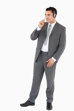 Young businessman with headset on against a white background photo