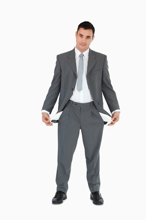 Businessman with empty pockets against a white background photo