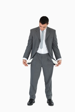 Businessman looking at empty pockets against a white background photo