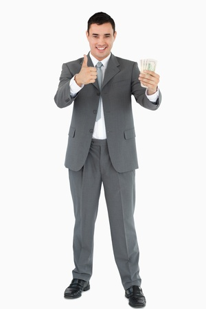 Businessman with banknotes giving thumb up against white background photo
