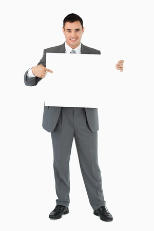 Businessman pointing at sign he is holding against a white background photo