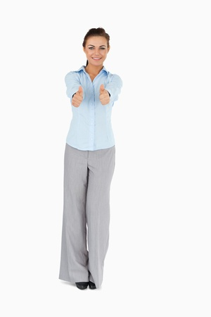 Smiling businesswoman giving thumbs up against a white background Stock Photo - 11623601