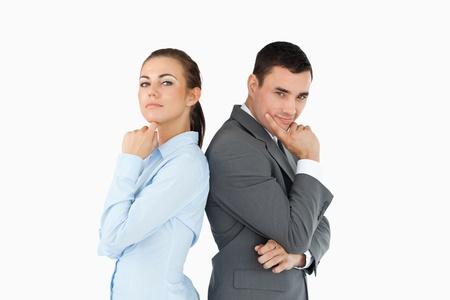 business rival: Los socios de negocios de back-to-back en los pensamientos sobre un fondo blanco Foto de archivo