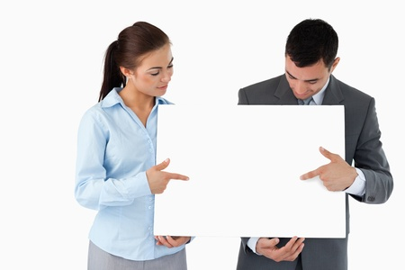Business partners pointing at sign they are presenting against a white background photo