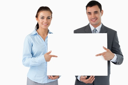 Business partners presenting sign together against a white background photo