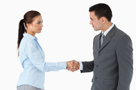 Business partners shaking hands against a white background photo