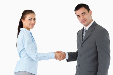 Young business partners shaking hands against a white background photo