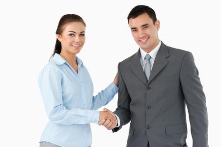 mani che si stringono: Soci d'affari sorridenti si stringono la mano su uno sfondo bianco