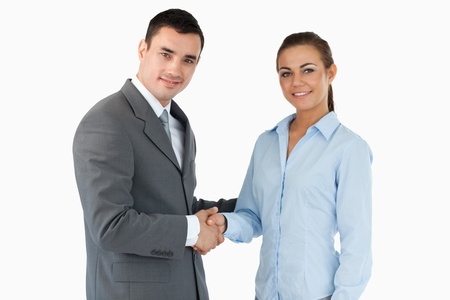 Smiling business partners closing a deal against a white background photo