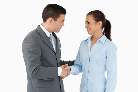 Young business partners closing a deal against a white background photo