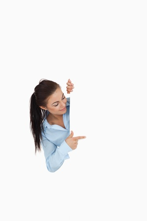 Businesswoman looking around the corner while pointing against a white background photo