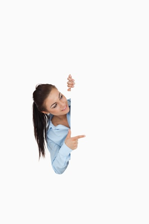 Businesswoman pointing while looking around the corner against a white background photo