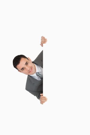 Businessman sneaking around the corner on white background Stock Photo - 11623577