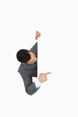 Businessman looking around the corner and pointing against a white background Stock Photo - 11623584