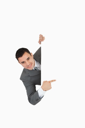 Businessman looking around the corner and is pointing against a white background photo