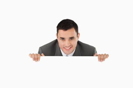 Businessman looking over wall against a white background Stock Photo - 11623590