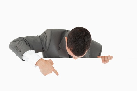Businessman pointing on sign below him against a white background Stock Photo - 11623844