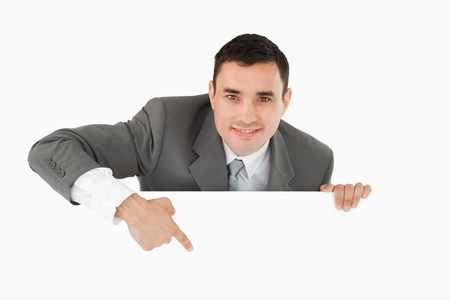 Businessman pointing at sign under him against a white background photo