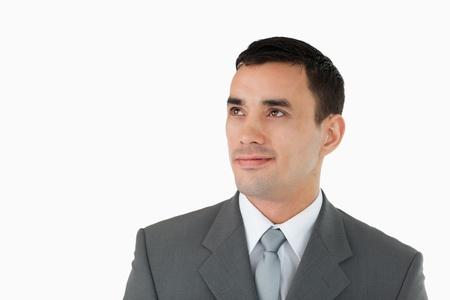 diagonally: Businessman looking diagonally upwards against a white background