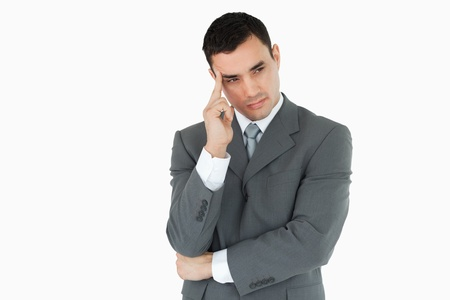 worried businessman: Businessman lost in thoughts against a white background