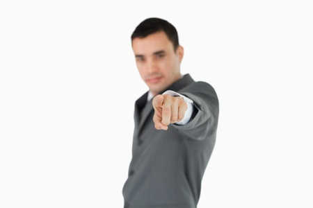 Side view of businessman pointing towards camera against a white background Stock Photo - 11623668