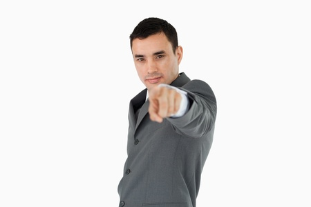 Side view of young businessman pointing towards camera against a white background Stock Photo - 11624294