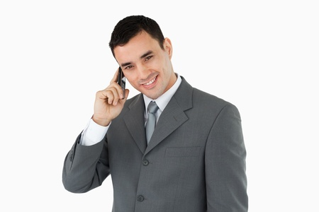 Smiling businessman on his phone against a white background photo