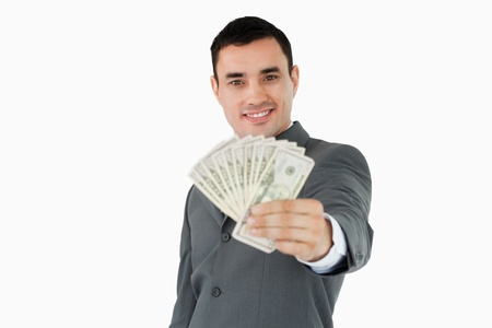 Smiling businessman presenting bank notes against a white background photo