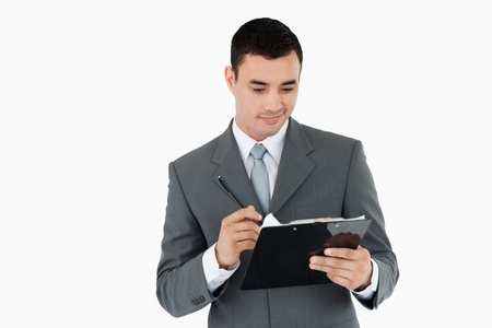 Businessman writing on clipboard against a white background photo