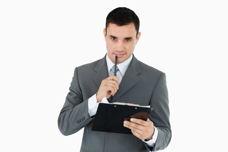 Businessman with pen and clipboard against a white background photo