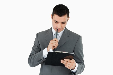 Businessman reading his notes on a clipboard against a white background photo