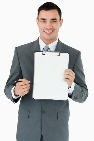 Smiling businessman pointing with pen at clipboard against a white background Stock Photo - 11635367