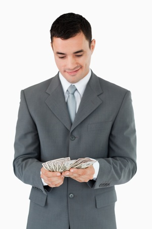 Businessman counting bank notes against a white background photo