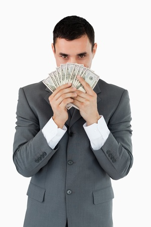 Businessman smelling bank notes against a white background photo