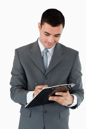 Businessman taking notes on clipboard against a white background photo