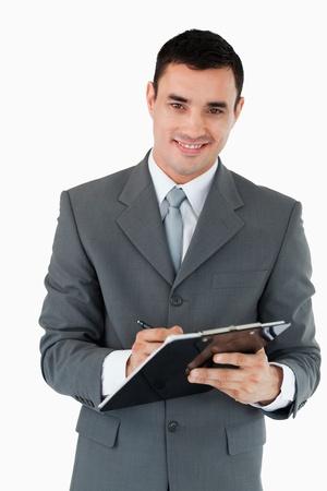 taking note: Smiling businessman prendere appunti su uno sfondo bianco