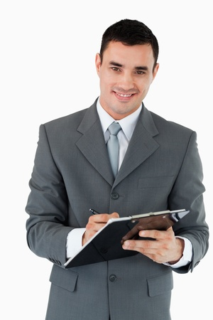 Smiling businessman taking notes against a white background photo