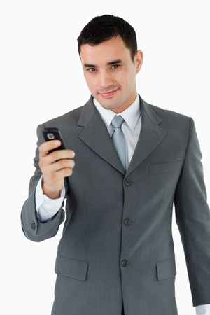 Confident businessman with his cellphone against a white background photo