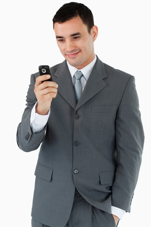 Smiling businessman looking at his cellphone against a white background photo