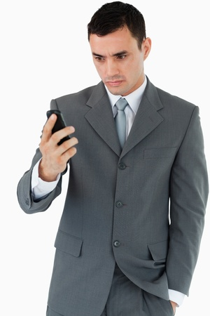 Serious looking businessman looking at his cellphone against a white background photo