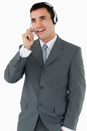Male call center agent looking upwards while talking against a white background photo