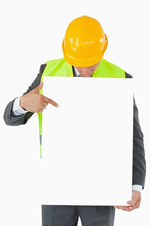 Architect looking and pointing on sign in his hands against a white background photo