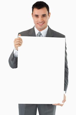 Businessman presenting sign against a white background photo