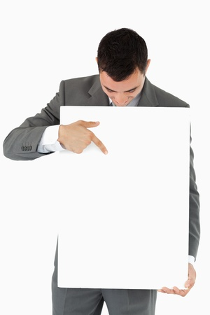 Businessman pointing at sign he is presenting against a white background Stock Photo - 11623842