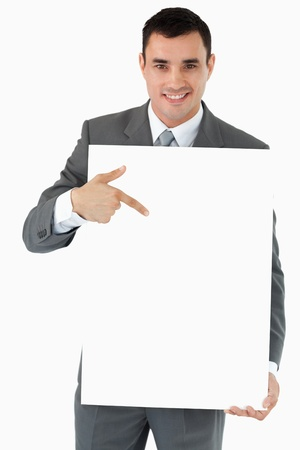 Smiling businessman pointing at the sign in his hands against a white background Stock Photo - 11623772